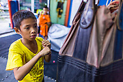 "18 DECEMBER 2104 - BANGKOK, THAILAND: A boy works out at the Kanisorn boxing gym. The Kanisorn boxing gym is a small gym along the Wong Wian Yai - Samut Sakhon train tracks. Young people from the nearby communities come to the gym to learn Thai boxing. Muay Thai (Muai Thai) is a Thai fighting sport that uses stand-up striking along with various clinching techniques. It is sometimes known as ""the art of eight limbs"" because it is characterized by the combined use of fists, elbows, knees, shins, being associated with a good physical preparation that makes a full-contact fighter very efficient. Muay Thai became widespread internationally in the twentieth century, when practitioners defeated notable practitioners of other martial arts. A professional league is governed by the World Muay Thai Council. Muay Thai is frequently seen as a way out of poverty for young Thais and Muay Thai camps and schools are frequently crowded. Muay Thai professionals and champions are often celebrities in Thailand.     PHOTO BY JACK KURTZ"