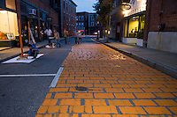 Painting Canal street for the transformation to PumpCanaly for Pumpkin Fest 2015.  Karen Bobotas for the Laconia Daily Sun