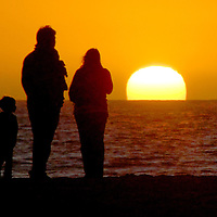 A family looks at the sun set at Santa Monica Beach on Tuesday, October 26, 2010..