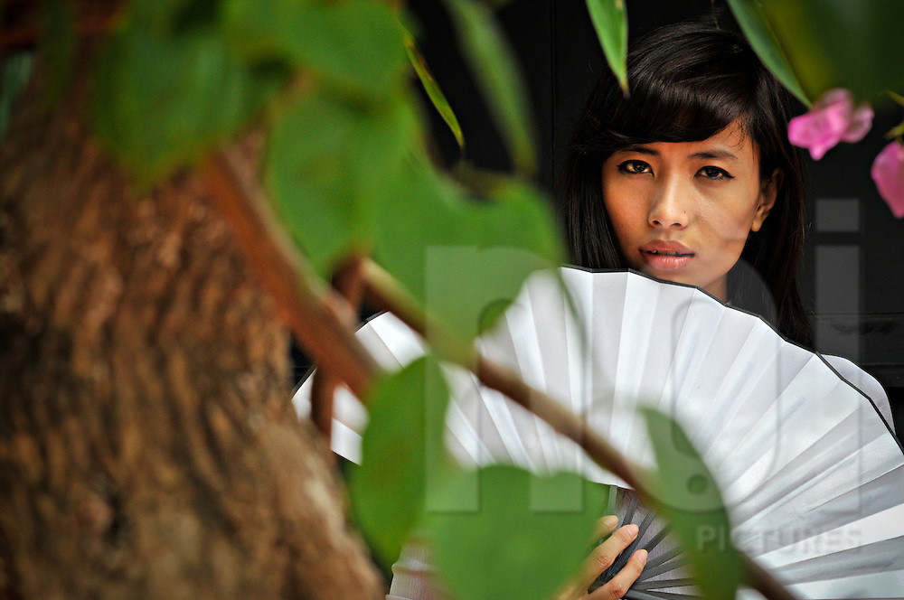 Portrait of a young Vietnamese woman seen through a flowering tree, Khanh Hoa province, Vietnam, Southeast Asia