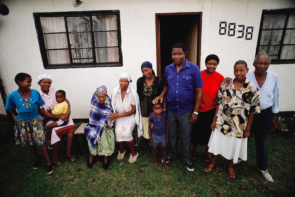 Simon and Poppy Qampie (center in blue shirt, and red, respectively) pose with their children and extended family outside their home outside Johannesburg, in Southwest Township, South Africa. The Qampie family lives in a 400 square foot concrete block duplex house in the sprawling area of Southwest Township (called Soweto), outside Johannesburg (Joberg) South Africa. Material World Project.
