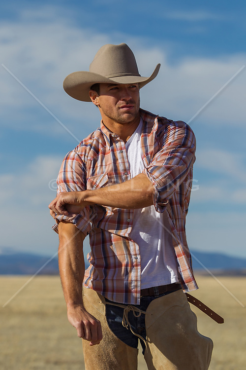 cowboy rolling up his sleeves on a ranch