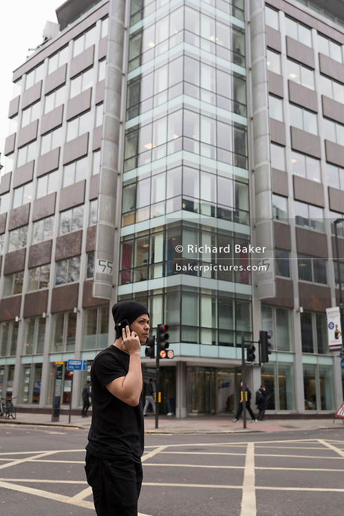 The day after Facebook's Mark Zuckerberg faced Senate Committee questions in Washington, a man uses his mobile phone outside the offices of Cambridge Analytica on New Oxford Street, the UK tech company accused of harvesting the personal details of Facebook users (including Zuckerberg himself) in its data privacy scandal, on 11th April, 2018, in London, England.