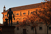 Statue of the architect Andres de Vandelvira, 1509–75, Spanish Renaissance architect, in the Vazquez de Molina Square, Ubeda, Jaen, Andalusia, Spain. Vandelvira designed many of the Renaissance buildings in Ubeda and Baeza. Behind the statue is the Palacio de las Cadenas or Palace of the Chains, or Vazquez de Molina Palace, designed by Andres de Vandelvira and built 1546-65 in Renaissance style for Juan Vazquez de Molina. The 3 storey building has a central portal, triangular pediments on the first floor windows, bull's eye windows and caryatids on the second floor and lanterns on the roof corners. The Renaissance buildings of Ubeda and Baeza are listed as a UNESCO World Heritage Site. Picture by Manuel Cohen