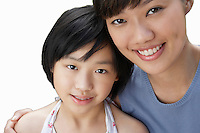 Close-up of sisters smiling over white background