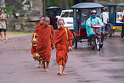 SIEM REAP, CAMBODIA - AUGUST 08, 2008: Unidentified monks walk by the road in front of the Angkor Thom South gate in Siem Reap, Cambodia.