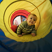 A ten month old baby girl playing in a toy play tunnel for kids. Photo Tim Clayton
