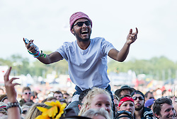 © Licensed to London News Pictures. 13/06/2015. Isle of Wight, UK.  A festival goer dances on his friends shoulders as he watches Jessie Ware perform at Isle of Wight Festival 2015 on Saturday Day 3.  Yesterday suffered torrential rain all afternoon and evening, after a first day of warm sun.  This years festival include headline artists the Prodigy, Blur and Fleetwood Mac.  Photo credit : Richard Isaac/LNP
