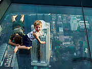 "27 DECEMBER 2018 - BANGKOK, THAILAND:  Children on the ""glass tray,"" a glass overlook that sticks out over the south edge of the Maha Nakhon Tower. The MahaNakhon Skywalk, at the top of the King Power Maha Nakhon Tower, is 1,030 feet (314 meters) above street level. It is the tallest building and highest vantage point in Bangkok. The skywalk opened in November and has been drawing large crowds.    PHOTO BY JACK KURTZ"