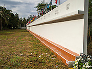 26 DECEMBER 2014 - MAE KHAO, PHUKET, THAILAND: The Tsunami Memorial Wall in Mae Khao, Phuket. The wall is located at the site that was used as the main morgue for people killed in the tsunami and hosts an annual memorial service. Nearly 5400 people died on Thailand's Andaman during the 2004 Indian Ocean Tsunami that was spawned by an undersea earthquake off the Indonesian coast on Dec 26, 2004. In Thailand, many of the dead were tourists from Europe. More than 250,000 people were killed throughout the region, from Thailand to Kenya. There are memorial services across the Thai Andaman coast this weekend.    PHOTO BY JACK KURTZ
