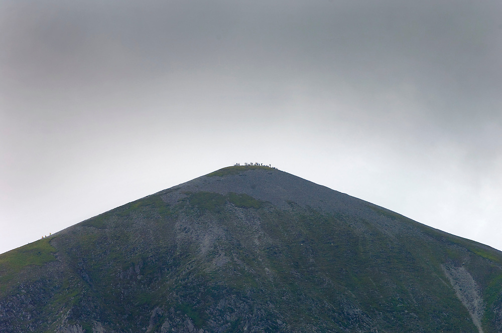 Pilgrims line the edge of the cone on croagh patrick during the annual pilgrimage which took place on Sunday. Pic: Michael Mc Laughlin
