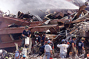 Ground Zero-Firemen use buckets and spray water on hot spots while looking for victims. 9/17/01