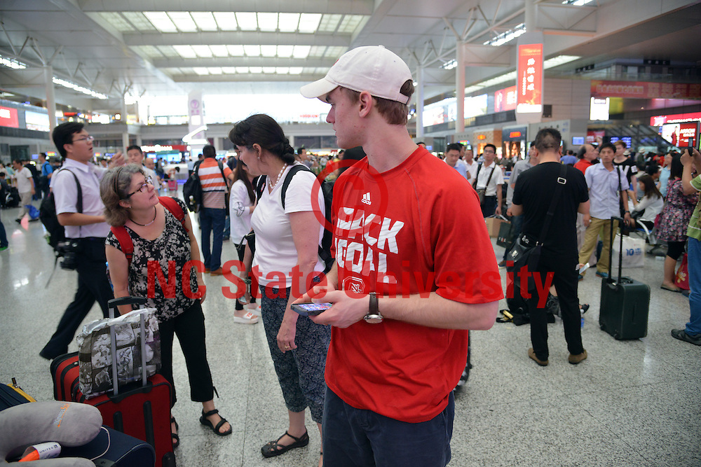Poole College of Management student Jake Forth and professors in the Shanghai train station.