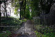 Gates lead to avenue of beech trees in Shipton-Under-Wychwood, The Cotswolds, UK