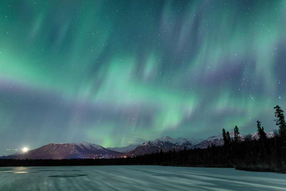 Moonrise as the Aurora Borealis (northern lights) dance above Beach Lake in Chugiak with the Chugach Mountains in the background. Winter. Evening.