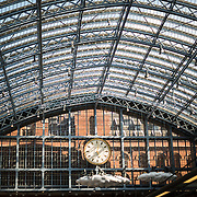 A large clock under the distinctive iron and glass arched cover over the platforms of St Pancras Railway Station (now known as St Pancras International). The renovated station features distinctive Victorian architecture and serves as a Eurostar terminal for high-speed trains to Europe. There are also platforms for domestic train services. The distinctive train shed roof was designed by William Henry Barlow.