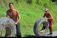 Rolling tires up a steep hill in the Jamal area, Guantanamo, Cuba.