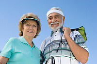 Senior couple holding tennis equipment, portrait