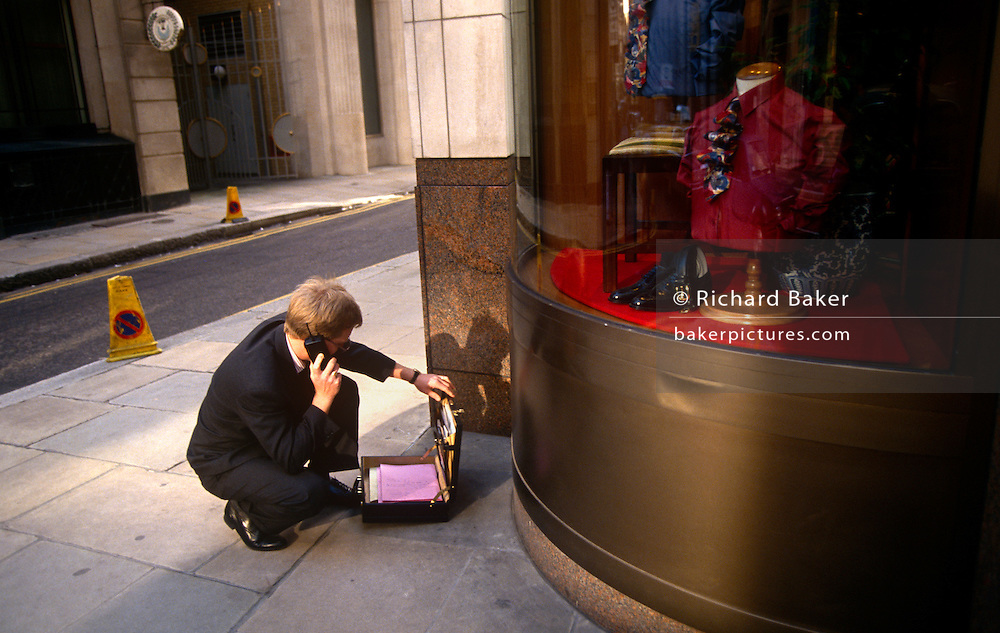 A city worker crouches on the pavement and opens his attache briefcase to check details written inside during his phone call conversation.  He is in the City of London, the capital's financial heart and makes his call using a 90s mobile (cell) phone in afternoon sunlight near a menswear shop on a street corner.