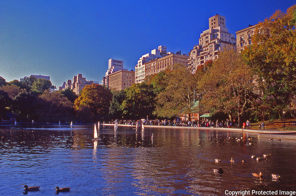 People enjoying model boats and the pond in Central Park on a colorful fall day in New York City