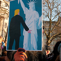 London UK. January 21st 2017.An estimated 100,000 protesters took part in a Women's March from the US Embassy in Grosvenor Square to Trafalgar Square as part of an international campaign on the first full day of Donald Trump's Presidency of the United States. A woman holds a placard showing a drawing of Donald Trump groping the Statue of Liberty.