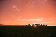 The sun peaks between Mongolian yurts on a hill silhouetted by sunset after a passing rain storm in the grasslands of Inner Mongolia.