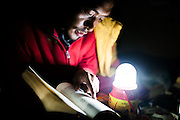 Lama Jamyang reading in the light of a solar powered lamp in his room in Komic Monastery in Spiti. Spiti sometimes experiences a power failure of more than a month in the winters and people rely on solar power for light.