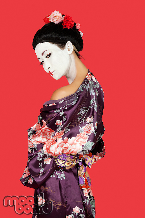Portrait of Japanese woman in kimono standing over red background