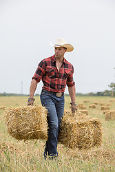 cowboy walking with hay bales in a field