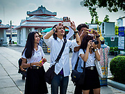 "11 SEPTEMBER 2017 - BANGKOK, THAILAND: Thai university students photograph the main entrance to Wat Arun. Renovations are nearly finished at Wat Arun on the Thonburi side of the Chao Phraya River in Bangkok. Wat Arun is famous for its Khmer style main ""prang"" (chedi). It was originally built in the Ayutthaya Period and rebuilt to its current form in the time of Rama II.     PHOTO BY JACK KURTZ"