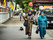 06 JULY 2016 - BANGKOK, THAILAND:  Women walk to Eid services at Ton Son Mosque in the Thonburi section of Bangkok. Eid al-Fitr is also called Feast of Breaking the Fast, the Sugar Feast, Bayram (Bajram), the Sweet Festival or Hari Raya Puasa and the Lesser Eid. It is an important Muslim religious holiday that marks the end of Ramadan, the Islamic holy month of fasting. Muslims are not allowed to fast on Eid. The holiday celebrates the conclusion of the 29 or 30 days of dawn-to-sunset fasting Muslims do during the month of Ramadan. Islam is the second largest religion in Thailand. Government sources say about 5% of Thais are Muslim, many in the Muslim community say the number is closer to 10%.       PHOTO BY JACK KURTZ