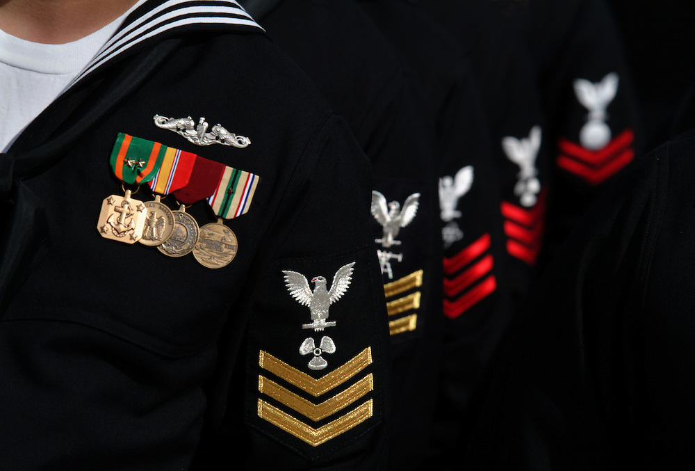 The Navy's different skill rates are specifically designed and stitched between the eagle and stipes on the left sleeve of the Navy blue dress uniform.