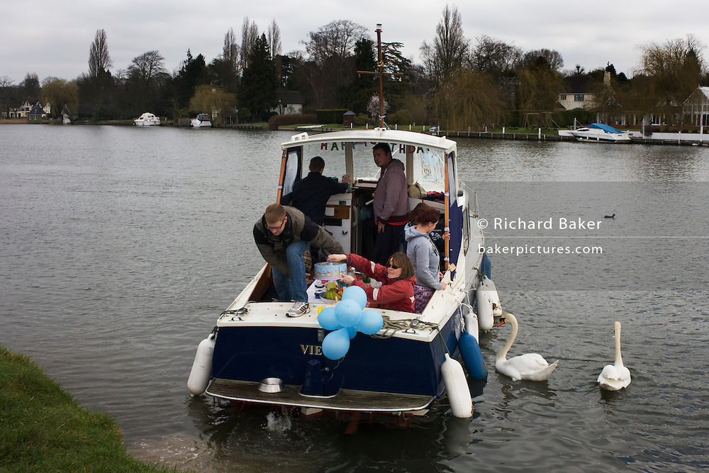 Friends out for a day's boating on the River Thames during a birthday party celebration at Cookham, Berkshire.