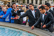 Sol3 Mio place poppies in the fountain after performing. A remembrance event in Trafalgar Square included a two minute silence and poppies being placed in the fountains.