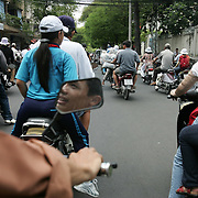 A decade ago Vietnams roads were teaming with bicycles. But as the countries economic growth increased bringing relative affluence to the working class, the push bike has been replaced by the scooter as the main mode of transport for the nations population.. Ho Chi Minh City alone has an estimated three million scooters buzzing around the streets day and night. Everyday life is dominated by the site of the scooter. Street corners have become parking lots for rows upon rows of parked scooters.. Puncture repair workmen wait on every city street to come to the aid of the rider with a blown tyre, and make a quick buck in the process, while families have a night on the town together, all seated on the same scooter!.Any number of items can be seen transported on the back of a scooter, from pigs to wardrobes anything that can be tied down is moved on the trusted scooter..Even in the outlying country areas the scooter is now used to transport produce to and from the markets. While even beach goers at the coastal towns head for a swim and a sunbathe accompanied by their scooter.  Street scene, Ho Chi Minh City, Vietnam.on September 29, 2006. Photo Tim Clayton