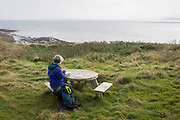 A visitor to Holy Island sits on a picnic table to read a book at a location overlooking the North Sea, on 27th September 2017, on Lindisfarne Island, Northumberland, England. The Holy Island of Lindisfarne, also known simply as Holy Island, is an island off the northeast coast of England. Holy Island has a recorded history from the 6th century AD; it was an important centre of Celtic and Anglo-saxon Christianity. After the Viking invasions and the Norman conquest of England, a priory was reestablished.