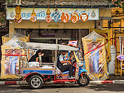 10 AUGUST 2016 - BANGKOK, THAILAND: A tuk-tuk (three wheeled taxi) in Bangkok drives past a shop selling portraits of Queen Sirikit. Thais are preparing for the Queen's birthday. Queen Sirikit of Thailand, was born Mom Rajawongse Sirikit Kitiyakara on 12 August 1932. She married  Bhumibol Adulyadej, King of Thailand (Rama IX) in 1950. He is the longest serving monarch in the world and she is longest serving consort of a monarch. Her birthday, like the King's Birthday (which falls on Dec. 5),  is a national holiday in Thailand. Her birthday, August 12, is also celebrated as Mothers' Day in Thailand. Thais hang portraits of Queen Sirikit in their homes and fly her royal flag on her birthday.        PHOTO BY JACK KURTZ