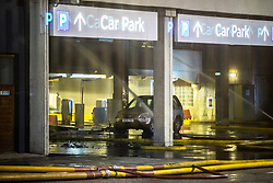 © Licensed to London News Pictures . 01/01/2018. Liverpool, UK. Fire hoses spray water inside the entrance to the car park which runs underneath an apartment block . Scene at the Liverpool Echo Arena car park where firefighters are working to extinguish a fire that started late on New Year's Eve and that destroyed all 1,400 cars parked in the multi-story car park. The Liverpool International Horse Show taking place at the Arena was abandoned and people and horses evacuated as dozens of fire crew worked to control the blaze . Photo credit: Joel Goodman/LNP