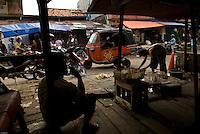 Man smoking in a market in Jakarta, Indonesia.<br /> Homme qui fume dans un marché à Djakarta, Indonésie.