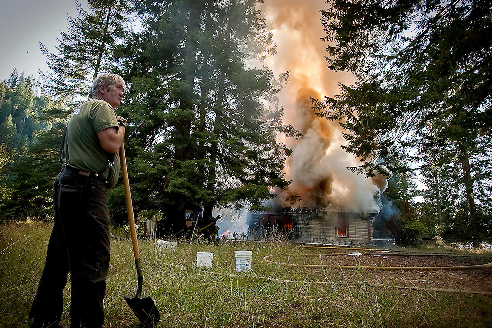 JEROME A. POLLOS/Press..Lynn Rasmussen watches arriving fire crews as a neighbor's log cabin is consumed by fire.