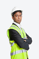 Portrait of confident Asian architect wearing reflective vest against white background