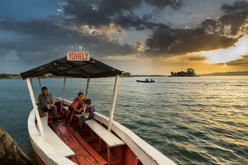 A family eats dinner in the setting sun of Lago Peten Itza. Flores, Guatemala