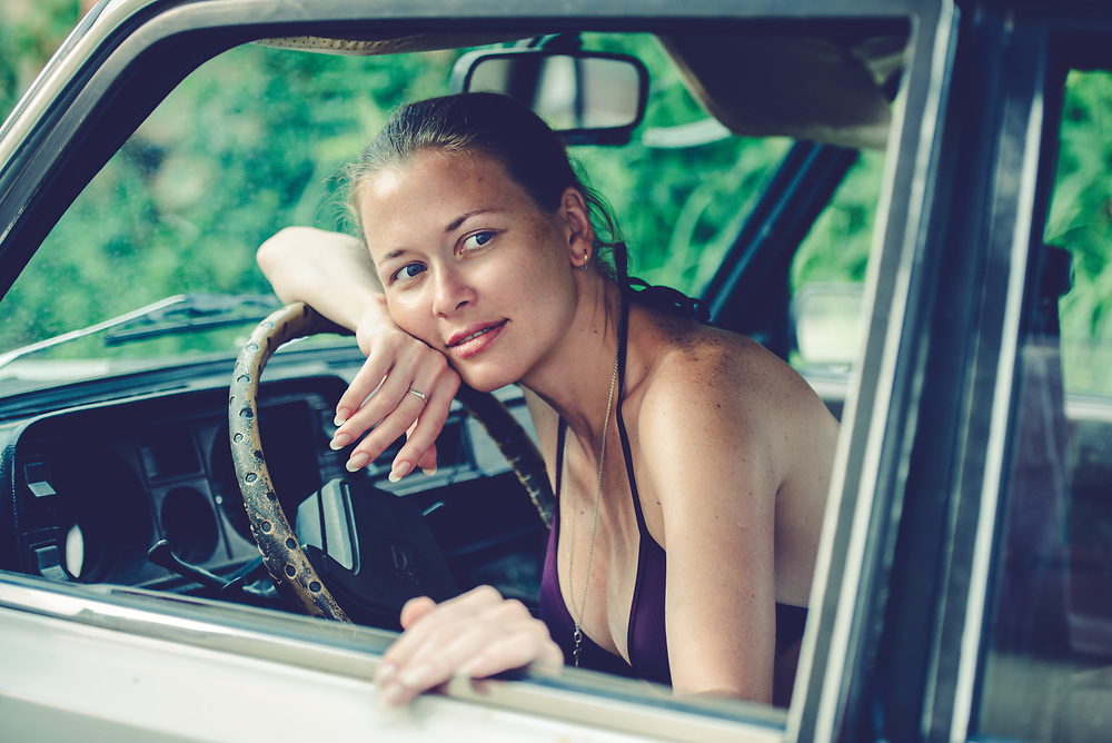 Portrait of a young woman in bikini leaning on a steering wheel of an old car.