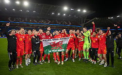 """CARDIFF, WALES - Tuesday, November 19, 2019: Wales' captain Gareth Bale (C) celebrates with his team-mates and a supporters' flag """"Wales. Golf. Madrid"""" after the final UEFA Euro 2020 Qualifying Group E match between Wales and Hungary at the Cardiff City Stadium. Wales won 2-0 and qualifyied for the Finals. (Pic by David Rawcliffe/Propaganda)"""