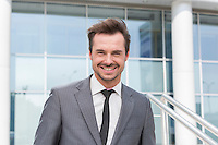 Portrait of happy young businessman standing outside office building