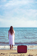 a girl in a white dress is standing on a beach and left a red suitcase behind her