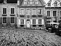 Galerie Place Royale and restaurant La Pizz in Royal Square on a rainy day. Beautiful historic architecture, French style houses in Old Quebec City. Quebec, Canada. Black and white. Place Royale, Ville de Québec.