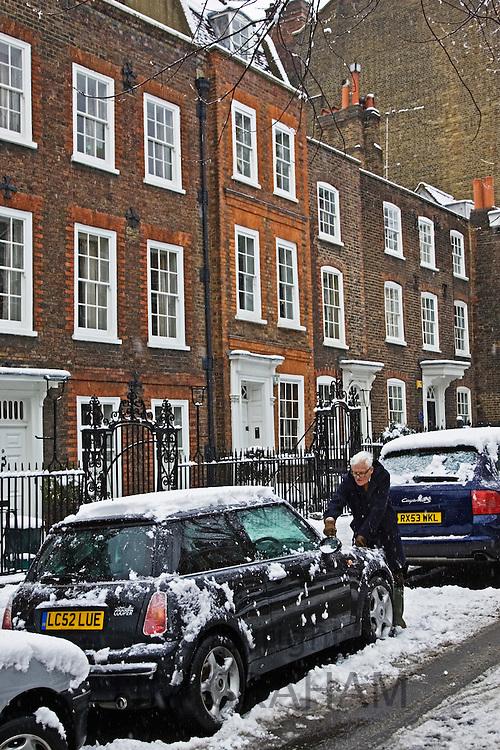 Man scrapes snow off Mini Cooper car parked in London street, Church Row, Hampstead, England, UK