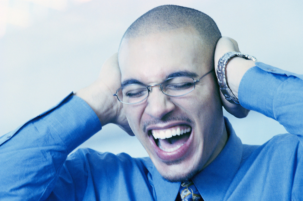 Closeup of man screaming and covering his ears&amp;#xA;<br />