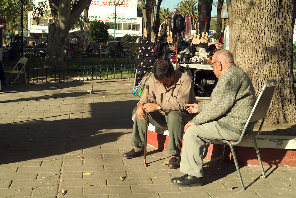 Men sit and talk in park in Tecate, Mexico